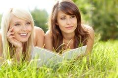 Twee jonge mooie glimlachende vrouwen die boek lezen Stock Foto's
