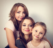 Twee jonge mooie glimlachende vrouwen en gelukkig jong geitjemeisje die verstand koesteren stock afbeelding