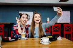 Twee jonge mooie hipstervrouwen die bij koffie, modieuze in uitrusting, de vakantie van Europa, gelukkige straatstijl zitten, heb Stock Foto's