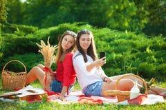 Twee jonge mooie meisjes die pret op de picknick hebben, die selfie op een smartphone maken royalty-vrije stock afbeeldingen