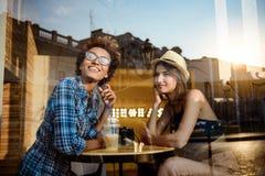 Twee jonge mooie meisjes die, spreken, die in koffie rusten glimlachen Van buiten geschoten Stock Fotografie