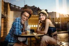 Twee jonge mooie meisjes die, spreken, die in koffie rusten glimlachen Van buiten geschoten Stock Foto's