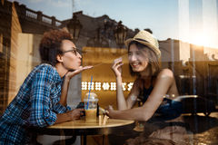 Twee jonge mooie meisjes die, spreken, die in koffie rusten glimlachen Van buiten geschoten Royalty-vrije Stock Fotografie