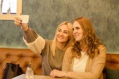 Twee jonge mooie meisjes gebruikend slimme telefoon en binnen makend selfie royalty-vrije stock foto