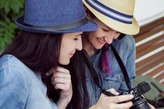 Twee jonge mooie meisjes in jeanskleding en hoeden zitten op een bank in het park op een achtergrond van groene installatiemuren, stock foto