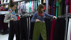 Twee jonge mooie meisjes kiezen kleren in een modieuze boutique _meisje zorgvuldig kijken bij de kleren en onder*zoeken het royalty-vrije stock afbeelding