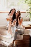 Twee jonge mooie meisjes met lang donker haar, die toevallige uitrusting dragen, zitten bij de treden en bekijken de telefoon in  royalty-vrije stock afbeeldingen