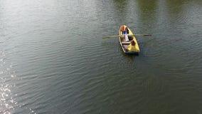 Twee jonge mooie meisjes zijn roeien in de kleine boot in het midden van mooi weerspiegelend meer of rivier ??n vrouw is stock video