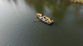 Twee jonge mooie meisjes zijn roeien in de kleine boot in het midden van mooi weerspiegelend meer of rivier ??n vrouw is stock footage