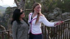 Twee jonge mooie vrouwen die fotograferen die slimme telefoon op de straat in het park met behulp van stock video