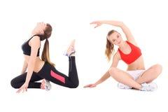 Twee jonge mooie vrouwen in zich sportenslijtage geïsoleerd uitrekken Stock Afbeeldingen