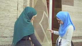 Twee jonge moslimvrouwen in hijabs kiezen tapijt stock footage