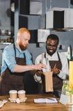 twee jonge multi-etnische eigenaars die van koffiewinkel orde zetten royalty-vrije stock afbeeldingen