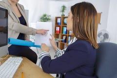 Twee jonge onderneemsters in bureau met document Stock Foto