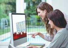 twee jonge onderneemsters die aan het ontwerp van het nieuwe bureau op de computer werken Royalty-vrije Stock Foto's