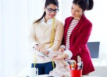 Twee jonge onderneemsters die in haar bureau werken Royalty-vrije Stock Afbeelding