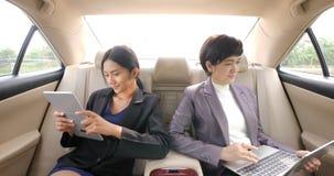Twee jonge onderneemsters met tabletcomputer en laptop in de achterbank van een auto stock footage