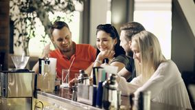 Twee jonge paren brengen tijd in een moderne bar door, heeft een groep vrienden pret en babbelt in afwachting van hun stock video