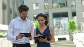 Twee jonge partners die aan de straat werken Partners die documenten en ideeën bespreken, die bevinden zich voor Royalty-vrije Stock Afbeelding