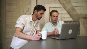 Twee jonge professionele mensen die koffie drinken kijken aan computer en bespreking stock footage