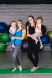 Twee jonge sportenmamma en baby girls do exercises samen in Stock Foto's