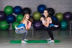 Twee jonge sportenmamma en baby girls do exercises samen in royalty-vrije stock afbeeldingen