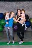Twee jonge sportenmamma en baby girls do exercises samen in stock afbeelding