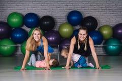 Twee jonge sportenmamma en baby girls do exercises samen in royalty-vrije stock afbeelding