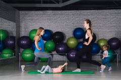 Twee jonge sportenmamma en baby girls do exercises samen in Stock Foto