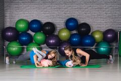 Twee jonge sportenmamma en baby girls do exercises samen in Stock Fotografie