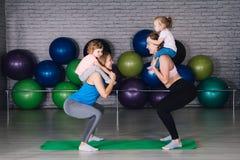 Twee jonge sportenmamma en baby girls do exercises samen in royalty-vrije stock foto