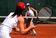 Twee jonge sportieve vrouwelijke tennisspelers die een spel in de zon hebben. Royalty-vrije Stock Afbeeldingen
