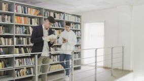 Twee jonge studenten die boek in bibliotheek lezen stock videobeelden