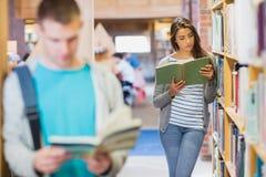 Twee jonge studenten door boekenrek in de bibliotheek Royalty-vrije Stock Afbeeldingen