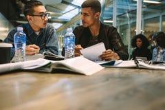 Twee jonge studentenstudies samen over een taak Klasgenoten die samen bij tablet met boeken en het bespreken zitten royalty-vrije stock foto