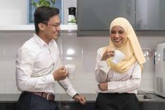 Twee jonge uitvoerende malay hebbend een onderbreking bij voorraadkast stock afbeelding