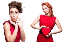 Twee jonge verraste vrouwen in rode kleding Royalty-vrije Stock Afbeeldingen
