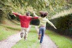 Twee jonge vrienden die op een weg in openlucht lopen stock foto's