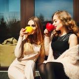Twee jonge vrij gelukkige vrouwenzitting in openlucht en drinkend coffe royalty-vrije stock fotografie