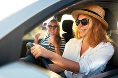 Twee jonge vrolijke glimlachende vrouwen in een auto op vakantie halen aan het overzeese strand over Meisje in glazen die een voe royalty-vrije stock foto's