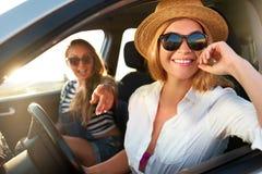 Twee jonge vrolijke glimlachende vrouwen in een auto op vakantie halen aan het overzeese strand over Meisje in glazen die een voe stock fotografie