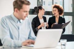 Twee jonge vrolijke vrouwelijke werknemers die in het bureau spreken stock afbeeldingen