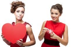 Twee jonge vrolijke vrouwen in rode kleding Royalty-vrije Stock Foto