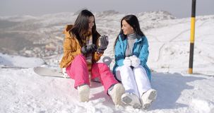 Twee jonge vrouwelijke snowboarders die van een praatje genieten stock videobeelden