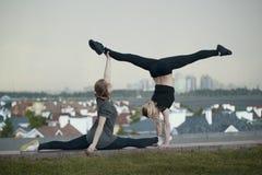 Twee jonge vrouwelijke turners die acrobatiekelementen met cityscape op achtergrond doen stock afbeeldingen