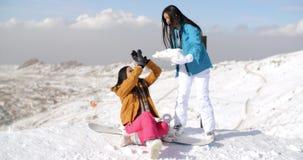 Twee jonge vrouwelijke vrienden die in de sneeuw spelen stock videobeelden