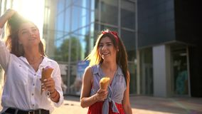 Twee jonge vrouwelijke vrienden die pret hebben en roomijs eten Het vrolijke Kaukasische roomijs die van vrouweneati in openlucht stock video
