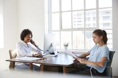 Twee jonge vrouwen aan het werk, aangaande de telefoon en lezingsdocumenten stock afbeeldingen