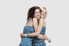 Twee jonge vrouwen in de aanpassing van sprongkostuums die elkaar over grijze achtergrond omhelzen Stock Afbeeldingen