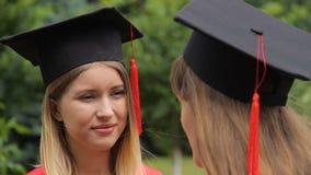 Twee jonge vrouwen die in academische kappen met leeswijzers na graduatie communiceren stock footage